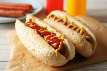 Tasty hot dogs on white wooden rustic background
