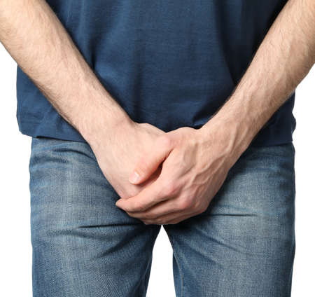 Man holds his crotch, isolated on white background Stock Photo