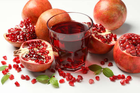 Pomegranate, juice and seeds on white background, close up