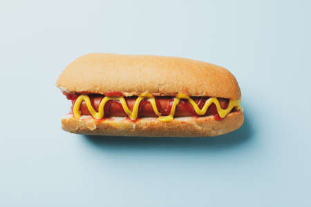 Tasty hot dog with sauces on blue background