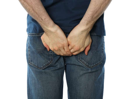 Man holding his butt, isolated on white background