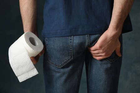 Man has diarrhea. Man holds toilet paper on blue background