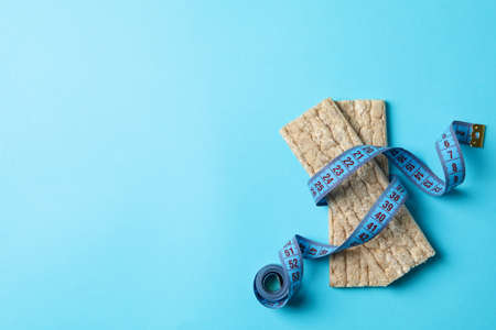 Measure tape and diet bread on blue background