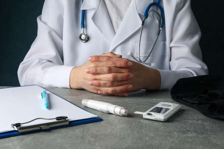 Doctor sits with folded arms. Diabetes test