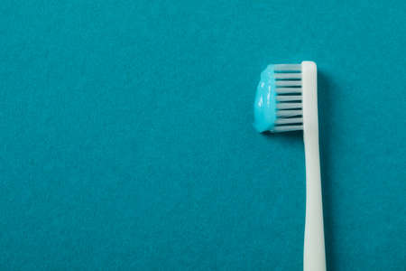 Toothbrush with toothpaste on turquoise background, space for text