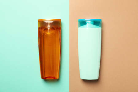 Blank bottles of shampoo on two tone background, space for text