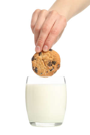 Woman dips cookies in a glass of milk, isolated on white background