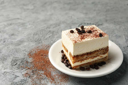 Composition with plate of tasty tiramisu on gray background