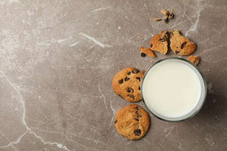 Chocolate chip cookies and milk on brown background, top view
