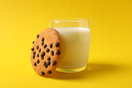 Chocolate chip cookies and glass of milk on yellow background