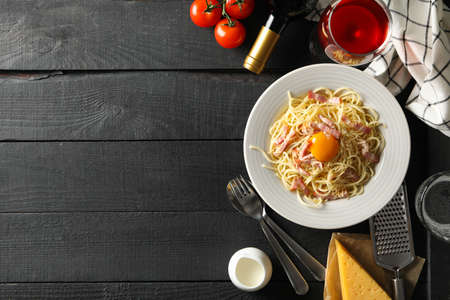 Composition with plate of tasty pasta and ingredients for cooking on wooden background Banque d'images