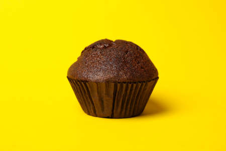 Tasty chocolate muffin on yellow background, close up