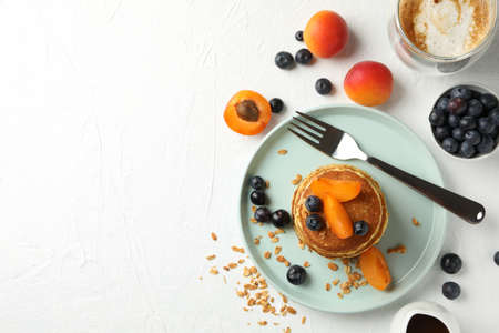Composition with pancakes and fruits on white background, top view