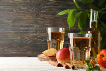 Composition with cider, cinnamon and apples on wooden background