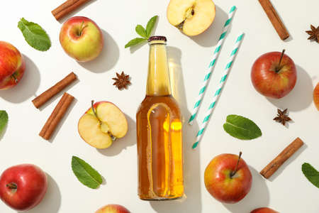 Composition with cider, apples, straws and cinnamon on white background Banque d'images