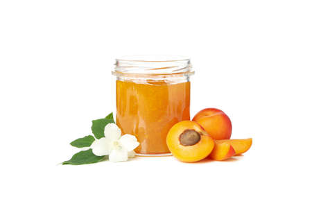 Glass jar with jam and apricots isolated on white background