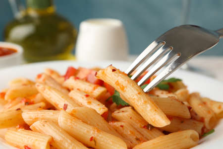 Composition with plate of tasty pasta and fork, close up