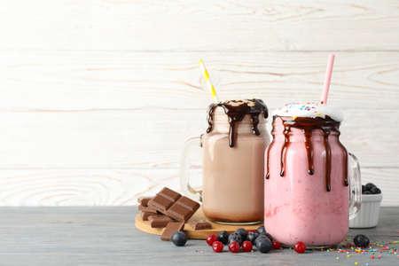 Delicious milkshakes on wooden background. Summer drink