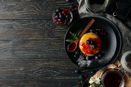 Plate of tasty pancakes with berry and powder on wooden table. Composition of sweet breakfast