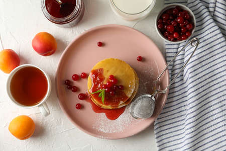 Composition with pancakes with jam and cranberry on white background Фото со стока