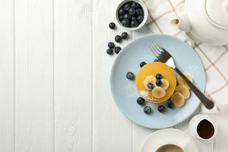 Composition with pancakes, banana and blueberry on wooden background. Sweet breakfast
