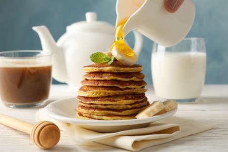 Woman pour honey on pancakes. Sweet breakfast