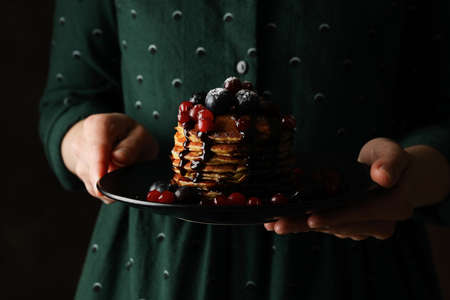 Woman holds plate with tasty pancakes against dark brown background, close up