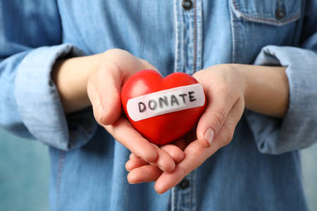 Woman holds heart on blue background, close up. Health care, organ donation