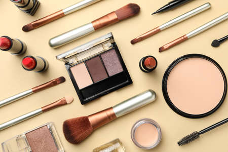 Different makeup cosmetics on beige background. Female accessories Imagens