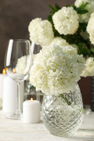 Composition with hydrangea flowers and candles against brown background. Romantic evening