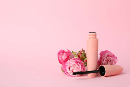 Macara and flowers on pink background. Female accessories 스톡 콘텐츠
