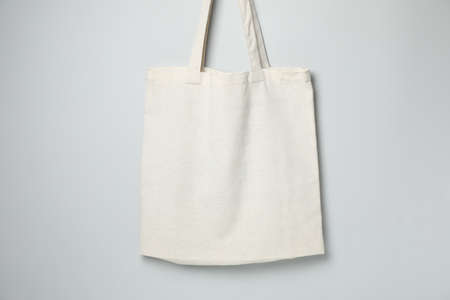 Empty white canvas bags on gray background, space for text. 免版税图像