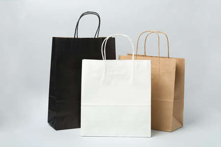 Empty paper bags on gray background, space for text.