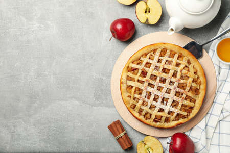 Composition with apple pie and ingredients on gray background, top view Standard-Bild