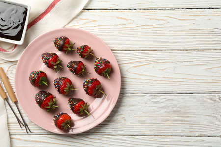 Chocolate fondue. Strawberry in chocolate on white wooden background