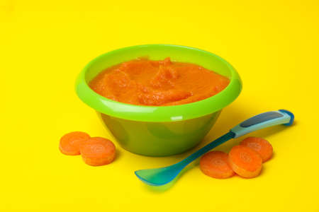 Bowl with vegetable puree on yellow background. Baby food Фото со стока