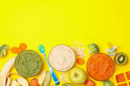 Composition with baby food on yellow background, top view