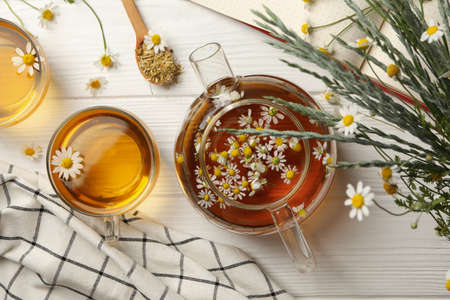 Composition with chamomile tea on white wooden background Banco de Imagens