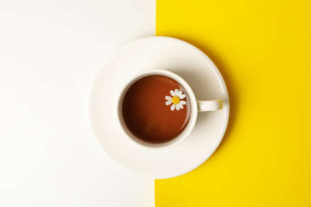 Cup of chamomile tea on two tone background, top view