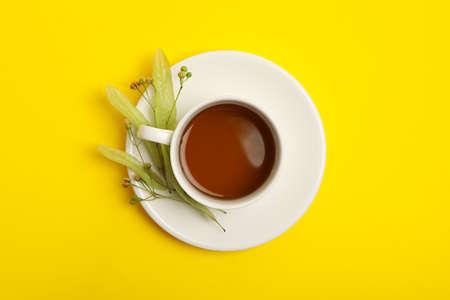 Cup of linden tea on yellow background, top view Stock fotó