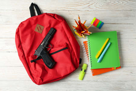 School accessories and gun on white wooden table. School violence 스톡 콘텐츠