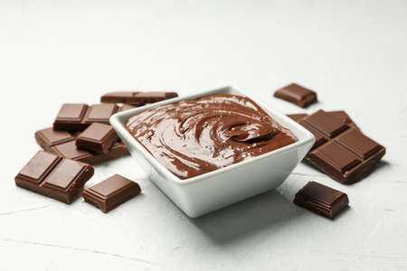Bowl with chocolate and chocolate pieces on white background
