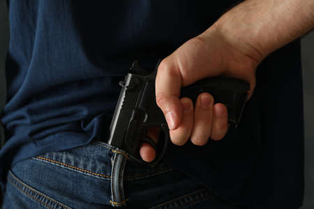 A man hold a gun from behind. Self defense weapon Stock Photo