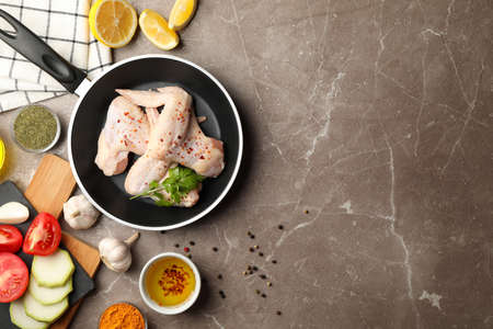 Composition with raw chicken and spices on gray background. Cooking chicken