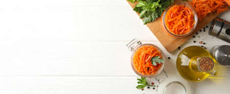 Composition with tasty carrot salad on white wooden background. Korean carrot
