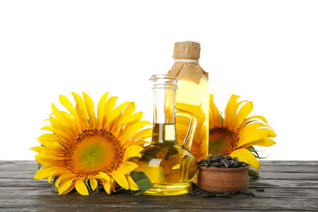 Composition with sunflower and oil on wooden table isolated on white background