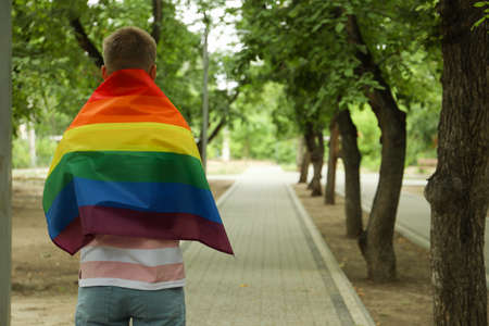 Young man with LGBT flag standing outdoor