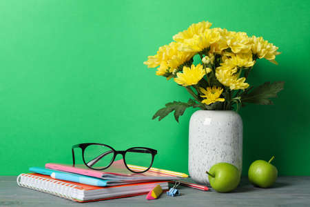 School supplies and vase with flowers on green background, space for text Imagens