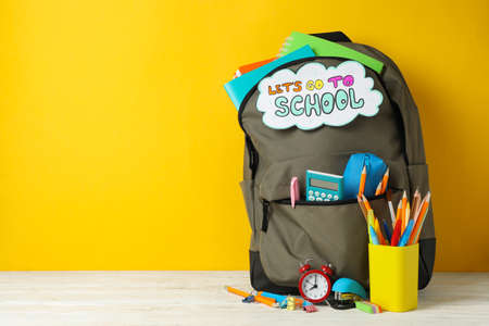 Text Let's go to school and school supplies on yellow background Imagens