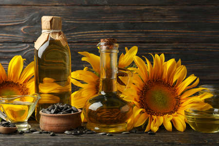 Composition with sunflower, oil and seeds on wooden background